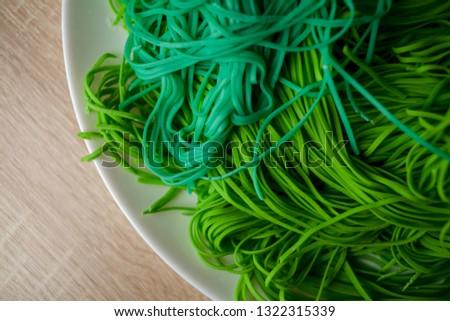 green vegetarian vermicelli. green vegetarian pasta. Vegetarian healthy food on white plate. green vegetarian pasta closeup photo #1322315339