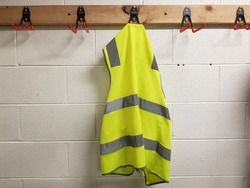Green vest hangs on the wall.