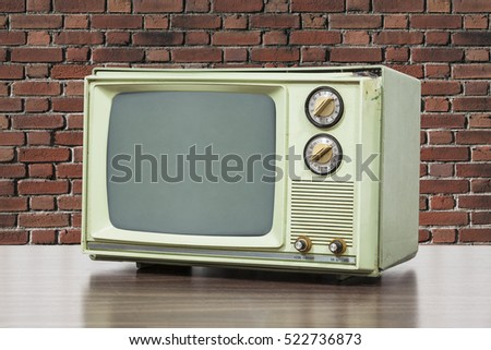 Green vintage television with brick wall. #522736873