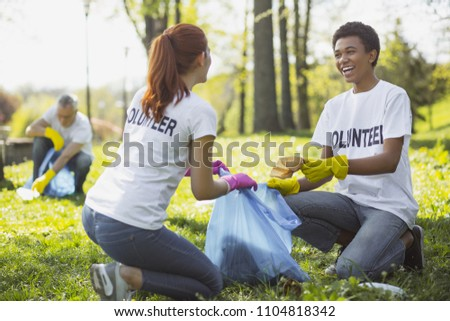 Green volunteering. Optimistic two volunteers holding garbage bag and communicating