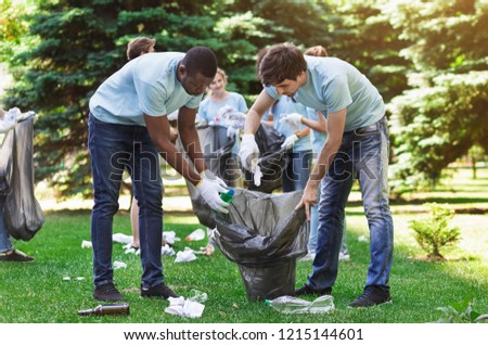Green volunteering. Two multiethnic men volunteers collecting garbage into bag in park, copy space