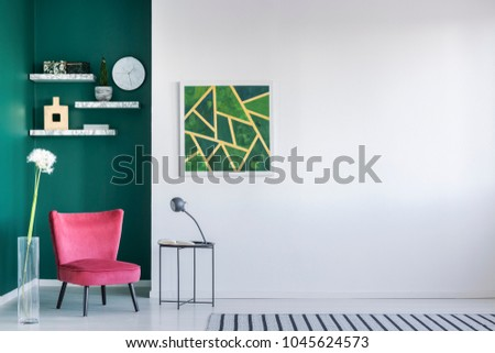 Green wall in a living room interior with pink armchair, painting, coffee table and striped rug #1045624573