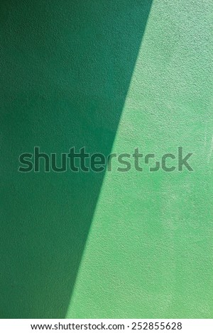Green wall of cement.light and shadow