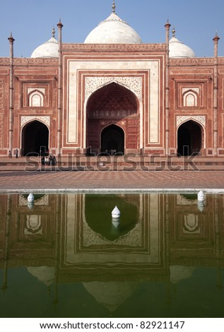 Green water mirrors red sandstone mosque with white domes and decorations. - stock photo