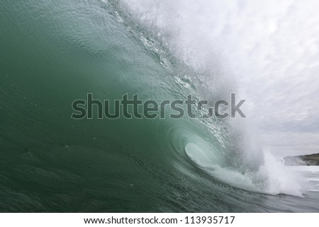 Green Wave/ an excellent shaped wave pitches and tubes, shot from the water, inside the wave #113935717