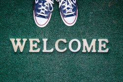 green welcome carpet with sneakers at a door