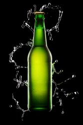 Green wet Bottle of beer on black background with water splash