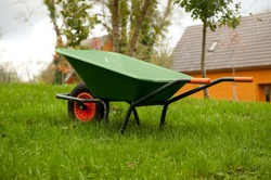 Green wheel barrow on the grass in the garden