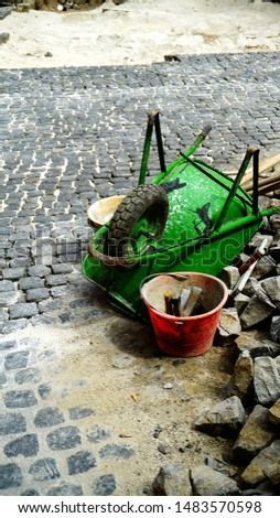 green wheelbarrow upturned in a construction site for stone brick flooring typical of many Italian cities