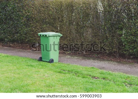 Green wheelie bin isolated next to a path and a green patch of Grass, UK.