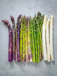 Green, white and purple asparagus on grey stone baclground