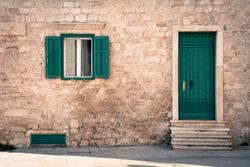 Green window and green door on old traditional house in Sibenik Croatia