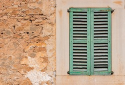 Green window shutters and grunge wall background.