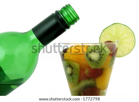 Green wine bottle and fruit glass with lime and wine, macro close up isolated on white, with copy space