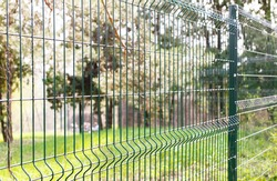 Green wire fence on background of green trees