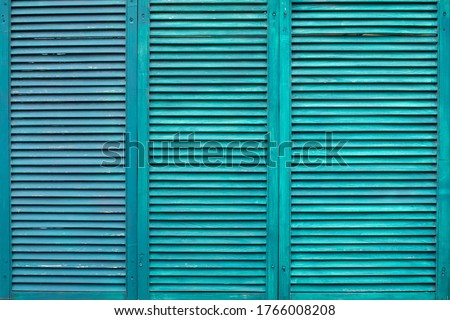 Green wooden shutters. Three wooden casement windows to block sunlight. Background with textured narrow boards of turquoise color. Old green wooden shutters tiled Stock photo ©