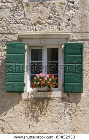 Green wooden, shutters with flowers on the Tisno house window