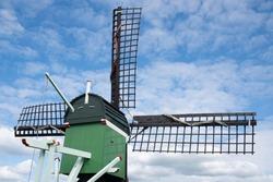 Green wooden windmill at a blue cloudy sky near the river Zaan in the Zaanse Schans, the Netherlands