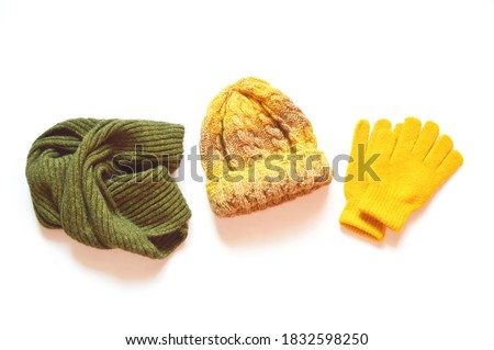 Green woolen scarf, yellow knitted hat and gloves isolated on a white background. Flat lay autumn and winter clothes. Bright accessories for stylish outfit Stock photo ©