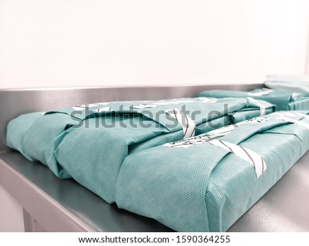 Green Wrapped Sterile Surgical Instrument Set On Table