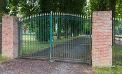 Green wrought iron gate between two masonry brick pillars