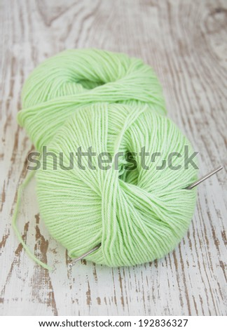 Green yarns and crotchet hook on a wooden background