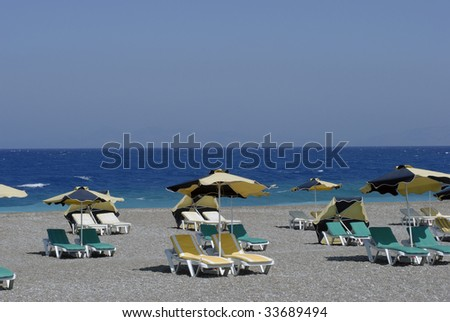 Green, yellow and black parasols and outdoor chairs close to the sea.