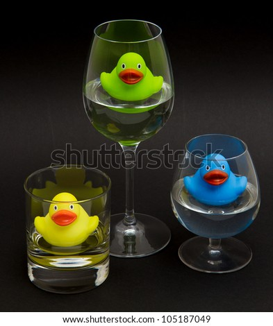 Green, yellow and blue rubber duck in different glasses on a dark background