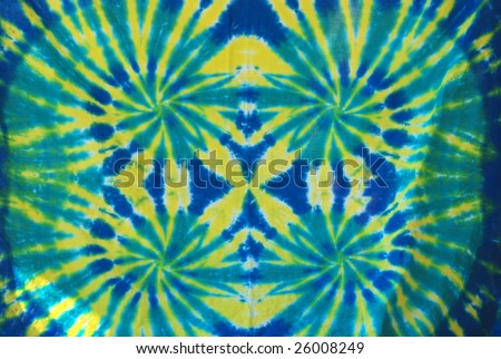 Green, yellow and blue tie dye design on fabric.