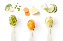 Green, yellow and orange baby puree in baby spoon isolated on white background, top view