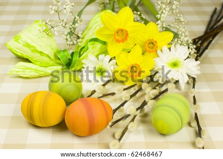 Green, yellow and orange easter eggs with a bunch of spring flowers - daffodils, chrysanthemum and catkins and green ribbon.