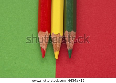 Green, yellow and red color pencil isolated in green and red background