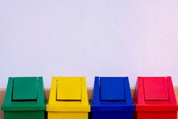 green, yellow, blue and red recycle bins