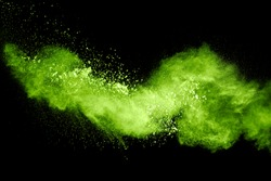 Green yellow dust particles explosion on black background. Powder dust splash.