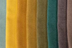 Green, yellow, gold, gray set of comparison interior decoration sample swaps of textured curtain fabric with various shades and colors and colorful backdrop evenly lit