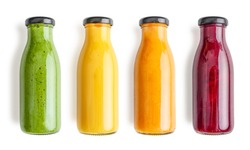Green, yellow, orange and red smoothie in glass bottles isolated on white background, top view. Clipping path included.
