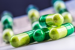 Green yellow pills or capsule freely laid on a white table.