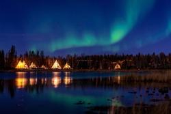 Greenish Aurora Borealis over illuminated Tipi near a lake, Yellow Knife, Canada