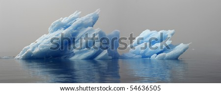 Greenland. Unusual blue ice among a dense fog on a still water.