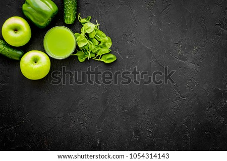 Greeny vegetable smoothie in glass on black background top view mock up
