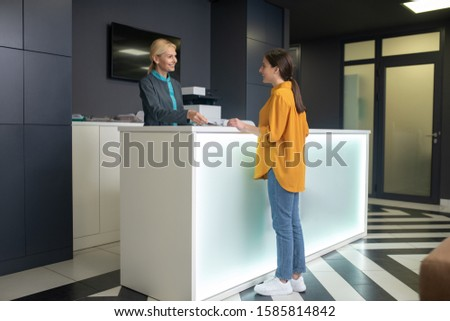 Greeting. Blond receptionist in clinic greeting a new comer