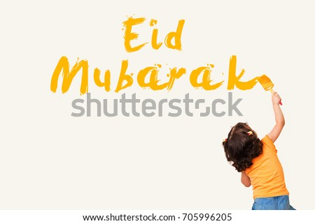 Greeting Card : Eid Mubarak - Arabic Translation : Blessed Feast - Muslim girl painting Eid Mubarak on the wall using paint brush #705996205