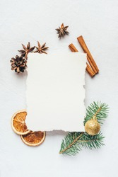 Greeting card for Christmas or New Yaer made of fir branche, spices and dried oranges and a cone with paper card note. Flat lay.