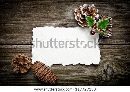 Greeting card for Christmas with pine cones and holly