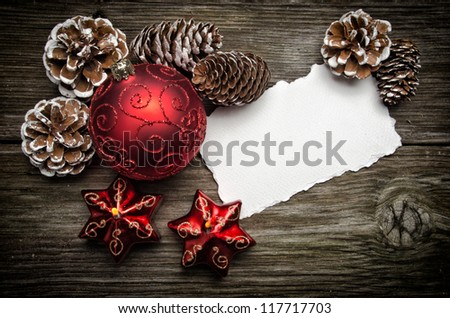 Greeting card for Christmas with red ball and candles on wooden top