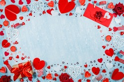 Greeting card for Valentine's Day. Red hearts, gift box, roses and candles on a blue background. Beautiful frame for text. Flatly. Copy the space. The concept of holiday and love.