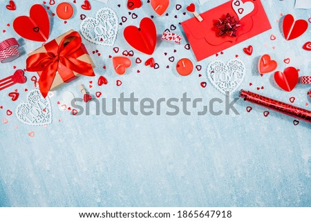 Photo of  Greeting card for Valentine's Day. Red hearts, gift box, roses and candles on a blue background. Beautiful frame for text. Flatly. Copy the space. The concept of holiday and love.