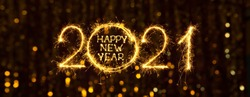 Greeting card Happy New Year 2021. Beautiful Wide Angle holiday web banner or billboard with Golden sparkling text Happy New Year 2021 written sparklers on festive bokeh background.