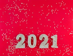 Greeting card of New Year 2021. Siver glitter figures and stars on a red background. Simple flat lay with copy space.