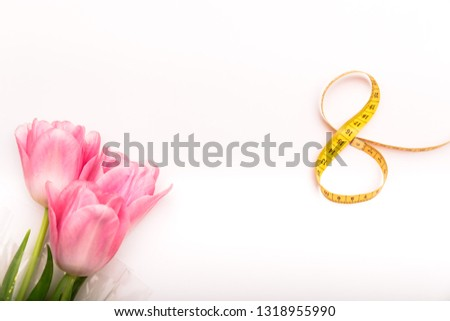 greeting card or background for the holiday of March 8 with flowers and centimeter tape